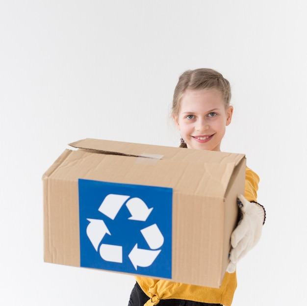 Retrato de menina sorridente segurando a caixa de lixeira