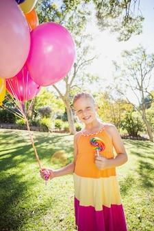 Retrato de menina sorridente segurando balões e pirulito no parque
