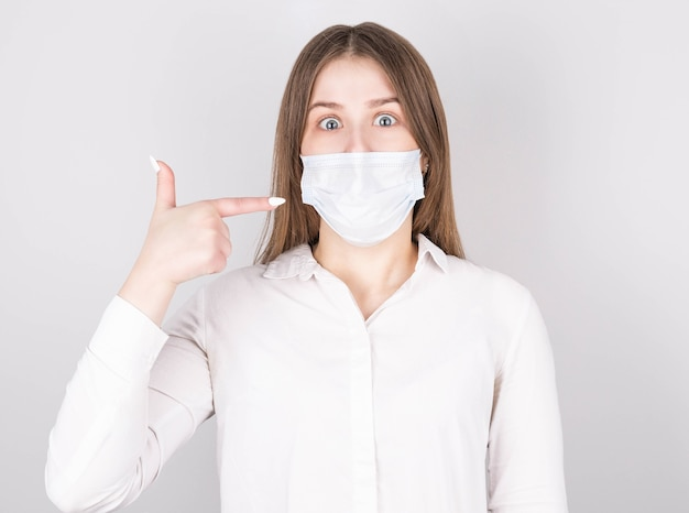 Retrato de menina surpresa com máscara médica e blusa aponta para as novas roupas de segurança covid-29, vestida em estilo casual, isolada em um fundo cinza
