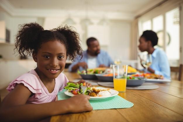 Retrato de menina tendo refeição na mesa de jantar