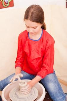 Retrato de menina tentando fazer cerâmica de argila branca em uma roda de oleiro
