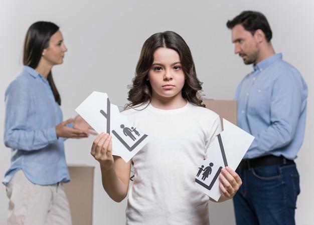 Retrato de menina triste com os pais discutindo por trás
