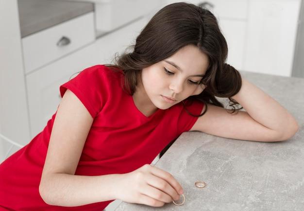 Retrato de menina triste olhando para anéis de casamento