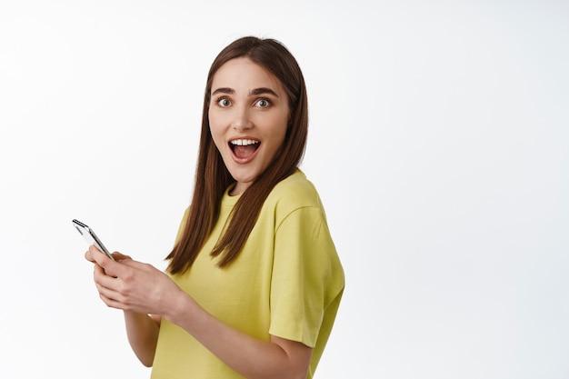 Retrato de menina usa smartphone, segura o celular, vira a cabeça e fica boquiaberta, reação a notícias incríveis online, grandes descontos no app em branco