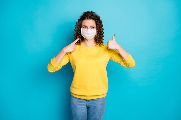Retrato de menina usando máscara de segurança medica o polegar para cima do seguro