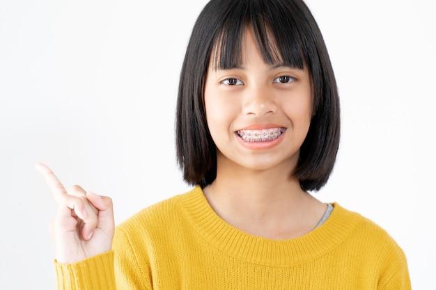 Retrato de menina vestindo amarelo swather com olhos pretos atraentes e aparelho dental sorrindo e feliz em branco