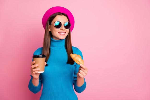 Retrato de menina viajar viagem positiva desfrutar café resto segurar para viagem caneca latte bebida delicioso croissant usar óculos de sol retrô azul boné.