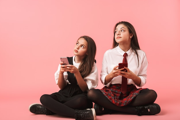 Retrato de meninas alegres em uniforme escolar, usando telefones celulares, enquanto está sentado no chão, isolado sobre a parede vermelha