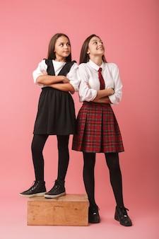 Retrato de meninas brancas com uniforme escolar em pé, isolado sobre uma parede vermelha
