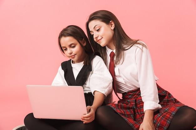 Retrato de meninas em uniforme escolar usando laptop, sentado no chão, isolado sobre a parede vermelha