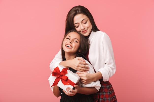 Retrato de meninas felizes em uniforme escolar segurando caixas de presente, em pé isolado na parede vermelha