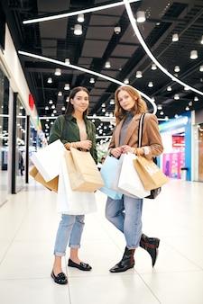 Retrato de meninas modernas em trajes casuais segurando muitos sacos de papel em um shopping center