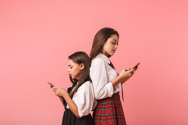 Retrato de meninas morenas em uniforme escolar usando smartphones, em pé isolado na parede vermelha