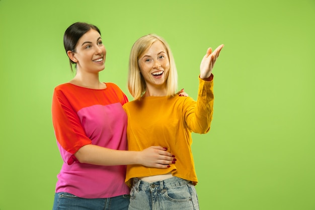 Retrato de meninas muito charmosas em roupas casuais, isoladas no espaço verde. duas modelos femininas namorando ou lésbicas