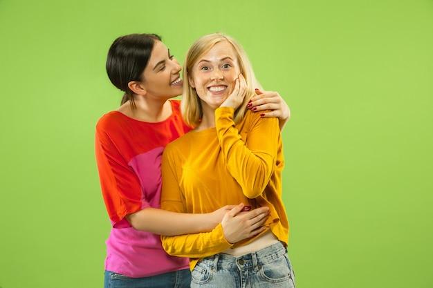 Retrato de meninas muito charmosas em roupas casuais, isoladas no fundo verde do estúdio. duas modelos femininas como namoradas ou lésbicas. conceito de lgbt, igualdade, emoções humanas, amor, relação.