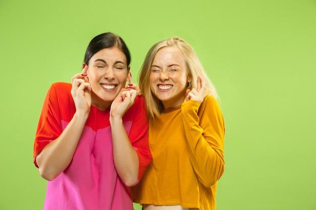 Retrato de meninas muito encantadoras em roupas casuais, isoladas no fundo verde do estúdio. duas modelos femininas como namoradas ou lésbicas. conceito de lgbt, igualdade, emoções humanas, amor, relação.