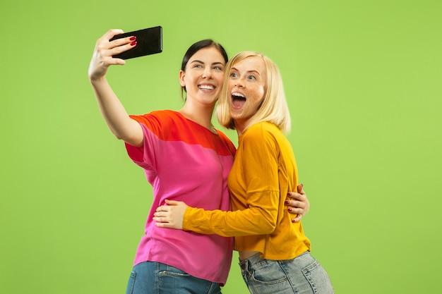 Retrato de meninas muito encantadoras em roupas casuais, isoladas no fundo verde do estúdio. namoradas ou lésbicas fazendo selfie. conceito de lgbt, igualdade, emoções humanas, amor, relação.