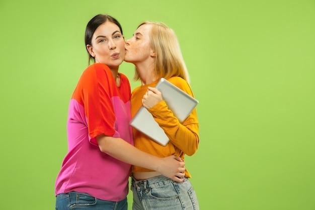 Retrato de meninas muito encantadoras em roupas casuais, isoladas no fundo verde do estúdio. namoradas ou lésbicas usando um tablet para se divertir ou pagamentos. conceito de lgbt, emoções humanas, amor, relação.