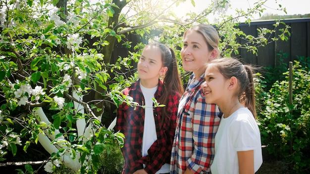 Retrato de meninas sorridentes com jovem mãe olhando árvores florescendo no pomar do jardim.