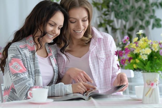 Retrato de meninas tomando café ou chá com o laptop em casa