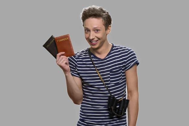 Retrato de menino adolescente alegre, mostrando seus passaportes. animado com a futura viagem. conceito de férias no exterior.
