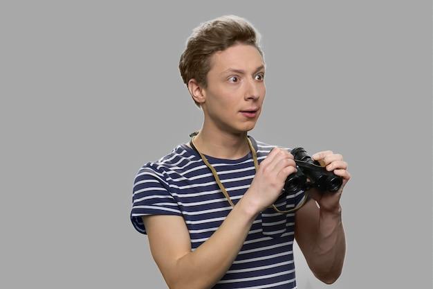 Retrato de menino adolescente chocado segurando binóculos. cara adolescente surpreso com binóculos contra um fundo cinza.