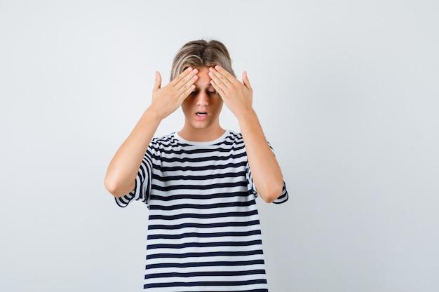 Retrato de menino adolescente com as mãos na testa em uma camiseta e olhando a vista frontal com medo