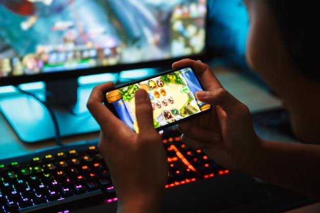 Retrato de menino adolescente jogando videogame no smartphone e no computador em um quarto escuro, usando fones de ouvido e um teclado colorido com luz de fundo