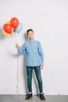 Retrato, de, menino adolescente, segurando, balões coloridos, em, mão
