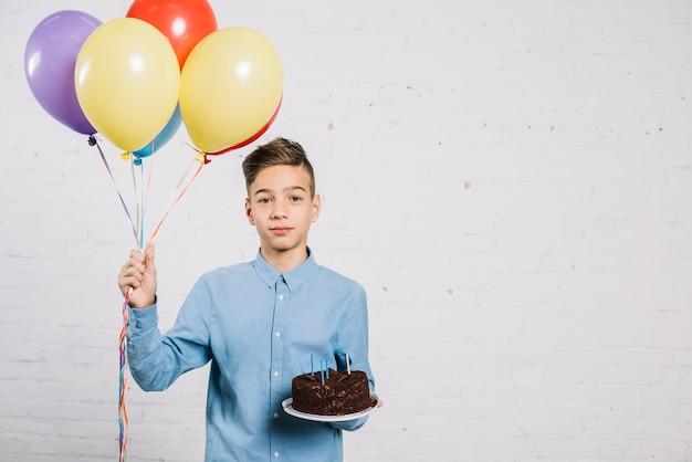 Retrato, de, menino adolescente, segurando, balões, e, bolo aniversário, contra, parede