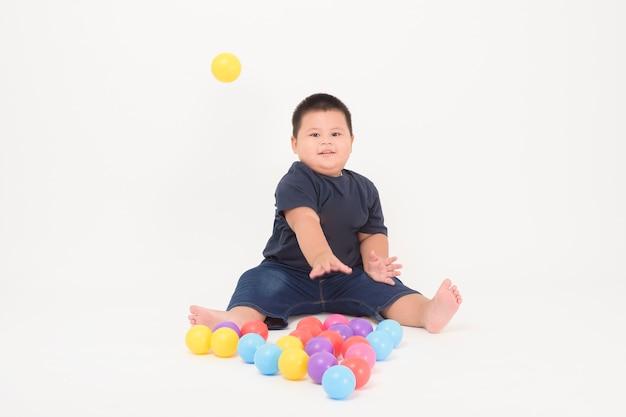 Retrato de menino adorável bonitinho está sentado e jogando bolas coloridas em branco
