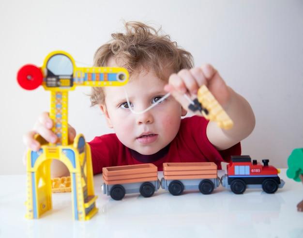 Retrato de menino adorável criança sentado à mesa brincando com um carro de construção de madeira em casa. criança com carrinho de brinquedo