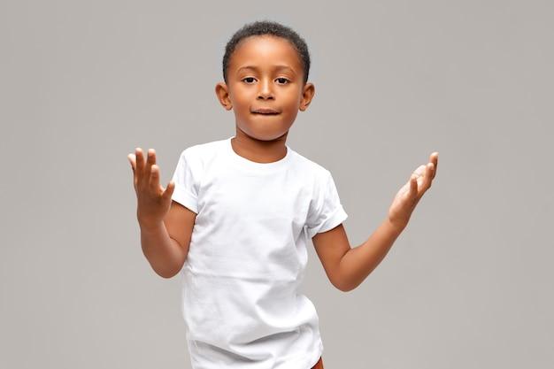 Retrato de menino afro-americano bonito legal vestido com camiseta branca casual, tendo uma expressão facial confiante, mostrando algum gesto com as mãos, mordendo o lábio inferior. crianças e conceito de estilo de vida