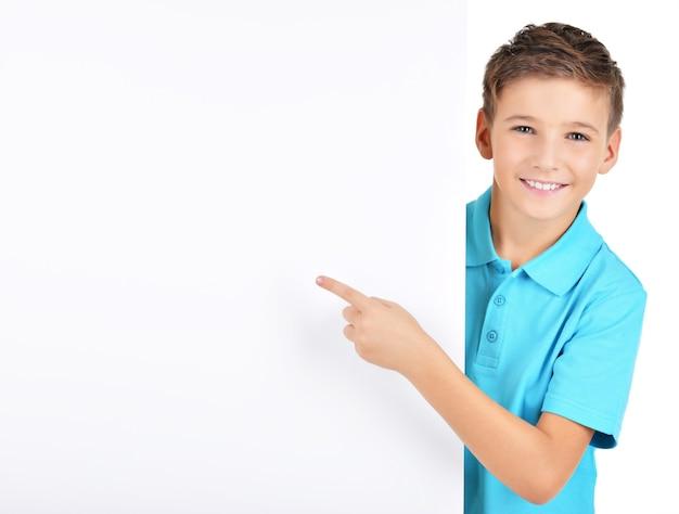 Retrato de menino alegre apontando em um cartaz branco isolado no branco