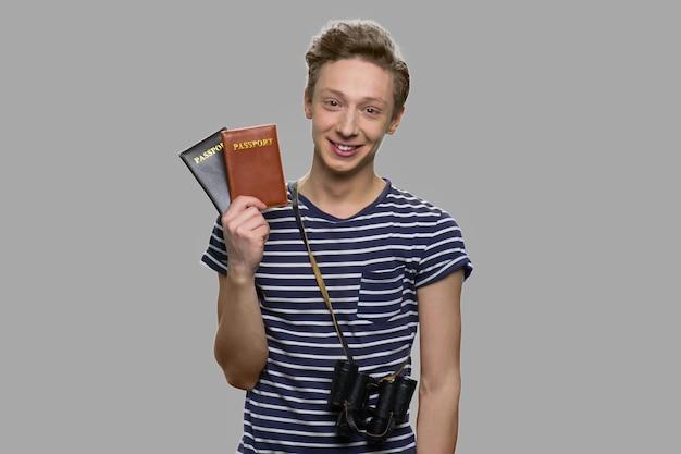 Retrato de menino alegre, segurando dois passaportes. turista de cara feliz olhando para a câmera.