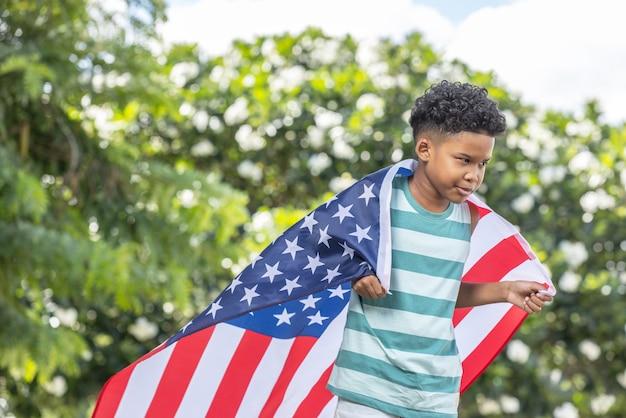 Retrato de menino americano de cabelo encaracolado com as costas drapeadas e cobertor com a bandeira americana