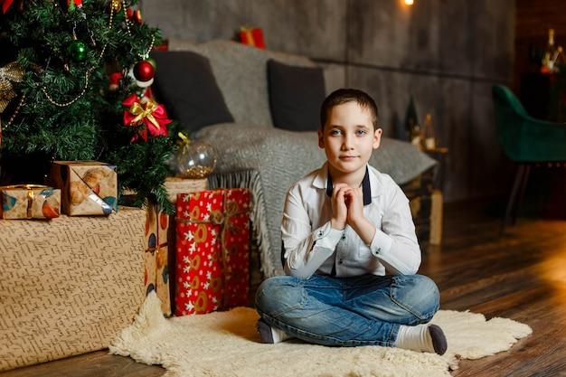 Retrato de menino animado abrindo presentes durante a véspera de natal em casa