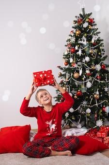 Retrato de menino animado segurando um presente de natal criança feliz em um pijama vermelho perto de uma árvore no natal