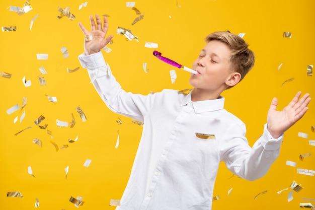 Retrato de menino aniversário. celebração divertida. garoto divertido soprando buzina de festa na chuva de confete isolada na parede laranja.