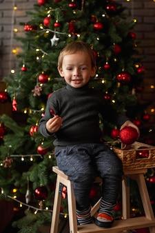 Retrato de menino ao lado da árvore de natal