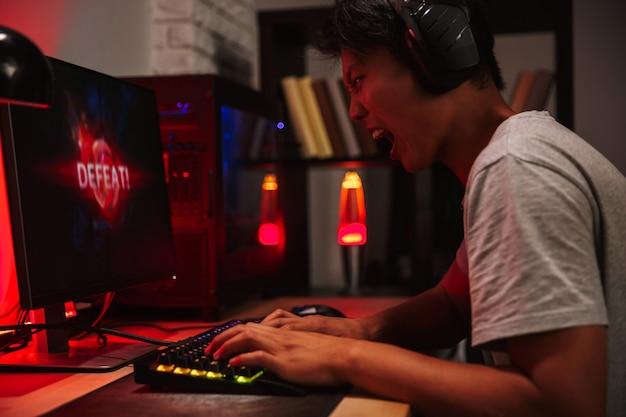Retrato de menino asiático tenso jogador com raiva perdendo enquanto jogava videogame no computador em um quarto escuro, usando fones de ouvido e teclado colorido com luz de fundo