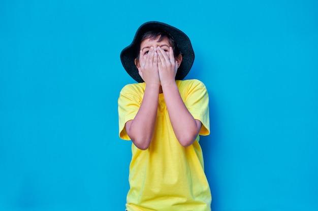 Retrato de menino assustado com as mãos cobrindo o rosto com uma camiseta amarela
