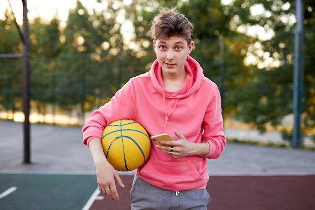 Retrato de menino basquete caucasiano com smartphone e bola nas mãos