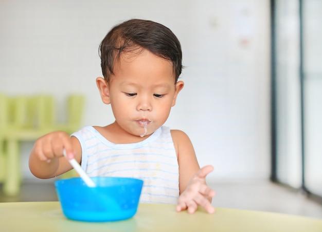 Retrato de menino bebê asiático comer cereais com flocos de milho e leite
