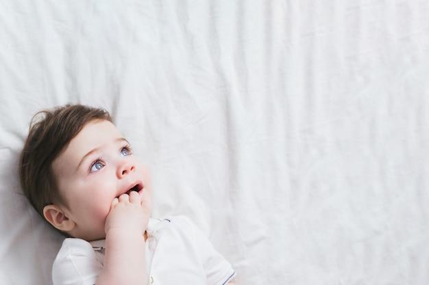 Retrato de menino bebê com expressão engraçada de rosto chocado e reação curiosa no fundo branco da cama