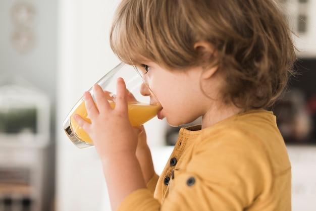 Retrato de menino bebendo copo de suco de laranja