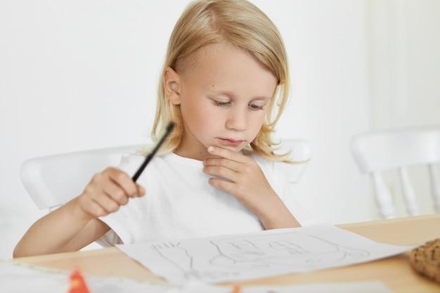 Retrato de menino bonitinho com cabelo solto loiro, sentado na cadeira à mesa de madeira, segurando o lápis e tocando o queixo, olhando seus desenhos. artesanato, criatividade, arte, pintura e conceito de infância