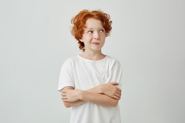 Retrato de menino bonitinho com cabelos ruivos e sardas em camiseta branca, olhando para longe, perseguindo os lábios, segurando as mãos cruzadas.
