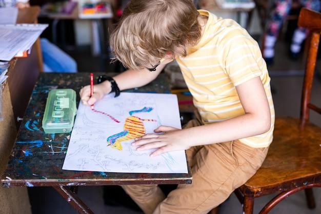 Retrato de menino bonitinho com caneta e papel de desenho na mesa na sala de aula