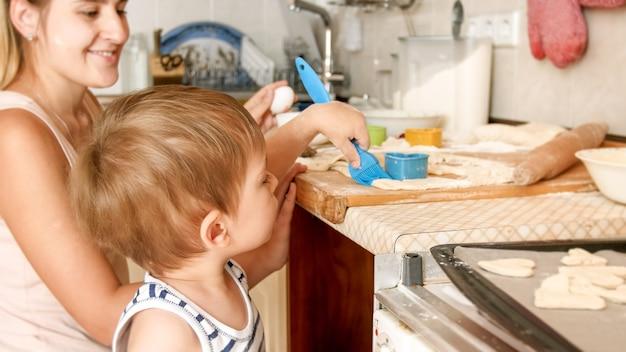 Retrato de menino bonitinho com jovem mãe fazendo biscoitos na assadeira na cozinha